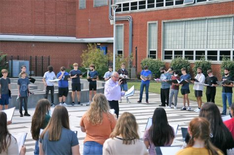 Dr. Brad Almquist directs the first district choir during rehearsal in the courtyard.